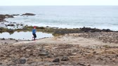 tory : Woman runs along the stony shore of the ocean. Healthy active lifestyle
