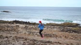 finish : Woman runs along the stony shore of the ocean. Healthy active lifestyle. Slow motion Stock Footage