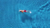 oynak : Aerial view of man in red shorts swims in the pool