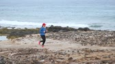pedregoso : Woman runs along the stony shore of the ocean. Healthy active lifestyle