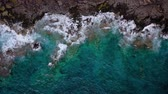 pedregoso : Top view of a deserted coast. Rocky shore of the island of Tenerife. Aerial drone footage of ocean waves reaching shore