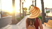 muhabir : Photographer tourist woman in a big yellow hat taking photos with camera in a beautiful tropical landscape at sunset Stok Video