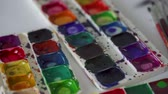 gribouillage : Brush takes different colors of watercolor paints from a palette and mixes them Vidéos Libres De Droits
