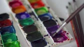 rabisco : Brush takes different colors of watercolor paints from a palette and mixes them Stock Footage