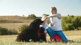 newfoundland : Mother and daughter having fun with their Newfoundland dogs on the nature