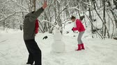 playful : Teenage couple making a snowman in winter snowy forest