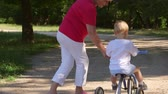 bike ride : Grandmother assisting grandson to ride a bicycle in the park Stock Footage
