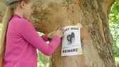 domestic : Child posting lost pet sign with dog image on on tree trunk Stock Footage