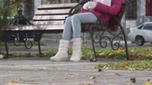 pavimentação : Autumn city scene teen girl listening music while sitting on a bench