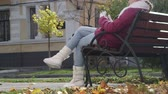 autumn : Girl sitting on a bench outside on a sunny autumn day