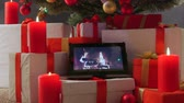 ribbon : Burning candles gifts boxes and tablet computer with fireplace on screen under Christmas tree