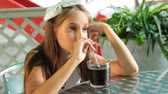 food and drink : Little girl drinking cola drink at outdoor cafe Stock Footage