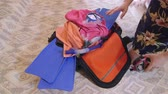 pack : Woman packing overfilled travel bag for summer getaways