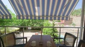 patio : Table with chairs on the terrace under folding awning in a sunny summer day tilt shot Stock Footage
