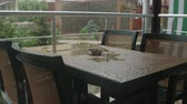 splashing : Table with chairs on the terrace in the rain Stock Footage
