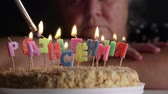 starość : Sad senior woman looking at birthday cake with lighting candles Happy Birthday in Russian Wideo