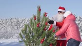 parent : Family decorates a Christmas tree in snow covered winter forest Stock Footage