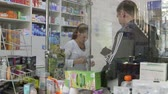adult : SIMFEROPOL, RUSSIA - CIRCA OCTOBER 2015: Female pharmacist serving man in drugstore pharmacy Stock Footage
