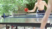 com sombra : Teenage boys have fun playing outdoor table tennis in the shaded court yard