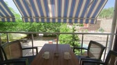 com sombra : Shaded balcony of summer hotel with outdoor table and chairs set in cooling shade of retractable awning