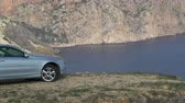 montanha : Two-door stylish coupe car parked on the edge of cliff at sea shore Stock Footage