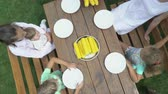 jantar : Top view of family enjoying an outdoor dinner eating boiled corn on the cob. Children have fun eats sweet corn cob at a wooden table on green grass lawn. Corn eating contest in the garden.