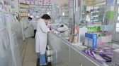 SIMFEROPOL, CRIMEA - CIRCA OCTOBER 2015: Pharmacy store interior. Female pharmacists working behind the counter at the drugstore. Woman professional pharmacist talking on the phone advising customer.