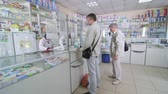 фармацевт : SIMFEROPOL, CRIMEA - CIRCA OCTOBER 2015: Pharmacy store interior. People buying medicines. Pharmacist behind the pharmacy counter serving customers at the drugstore. Стоковые видеозаписи