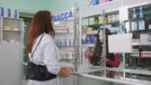 SIMFEROPOL, CRIMEA - CIRCA OCTOBER 2015: Retail pharmacy shop interior. Young woman buying medicines. Female pharmacist serving customer behind the counter display showcase.