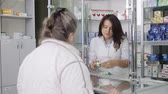 SIMFEROPOL, CRIMEA - CIRCA OCTOBER 2015: Retail pharmacy shop interior. Elderly woman buying medicines. Female pharmacist serving customer behind the counter display showcase. Stock Footage