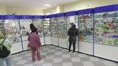 SIMFEROPOL, CRIMEA - CIRCA OCTOBER 2015: Retail pharmacy shop interior. People buying medicines. Pharmacy counter display showcase with medicines for sale at the drugstore.
