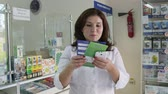 SIMFEROPOL, CRIMEA - CIRCA OCTOBER 2015: Female pharmacist reads medical brochure in front of pharmacy shelves in the drugstore. Woman health professional with healthcare leaflet talking at the camera