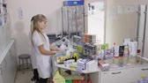 eczacı : SIMFEROPOL, CRIMEA - CIRCA OCTOBER 2015: Female pharmacists working behind the pharmacy counter at the drugstore. Team of pharmacists in white coats near pharmacy shelves with medicines.