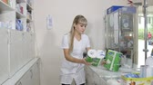 paper towel : SIMFEROPOL, CRIMEA - CIRCA OCTOBER 2015: Pharmacist working behind the pharmacy counter serving customers at the drugstore. Young woman pharmacist takes the medical paper towels off the shelf.