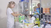 SIMFEROPOL, CRIMEA - CIRCA OCTOBER 2015: Pharmacist working behind the pharmacy counter serving customers at the drugstore. Woman buying paper towels at the hospital pharmacy.