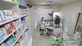 SIMFEROPOL, CRIMEA - CIRCA OCTOBER 2015: Pharmacy store interior. Drugstore shelves with medicines for sale. Young woman pharmacist serving customers. High angle shot.