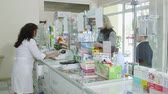 SIMFEROPOL, CRIMEA - CIRCA OCTOBER 2015: Pharmacy store interior. Female pharmacist behind the pharmacy counter serving customers at the drugstore.