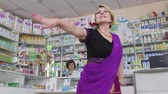 eczacı : SIMFEROPOL, CRIMEA - CIRCA OCTOBER 2015: Pharmacy store interior. Pharmacist and happy customer. Woman performing traditional indian dance at the drugstore.