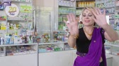SIMFEROPOL, CRIMEA - CIRCA OCTOBER 2015: Pharmacy store interior. Pharmacist and happy customer. Woman performing traditional indian dance at the drugstore.