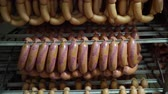 salsicha : YEVPATORIA, CRIMEA - CIRCA DECEMBER 2017: Meat and sausage manufacturing. Processed meat products in refrigerated warehouse of sausage making plant. Boiled sausages on racks in storage room.