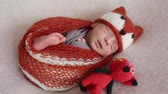fralda : A newborn boy wearing a fox dress is sleeping on a background of a stretched canvas Stock Footage