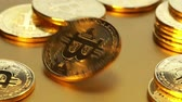 Coin golden bitcoin rotation, twist and falls on a golden background. Slow motion video 120 fps. Stock Footage