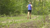 trial : Man running cross country in summer forest. Jogging motivation in green park beautiful inspirational landscape. Stock Footage