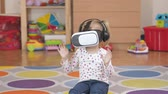technology : Girl wearing virtual reality goggles. Virtual reality game. The little girl with surprise and pleasure uses head-mounted display.