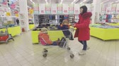 cartn corrugado : SAMARA, RUSSIA - February 9, 2017 Full Length Side View of family, Mother and her Children, Son and Daughter in Shopping Trolley Stock Footage