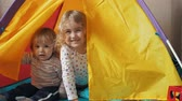 выглядывал : Little children look out of a childrens tent and laugh. Brother and sister playing in the nursery at home.
