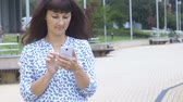 sólido : Text messaging. Woman using smartphone. Young attractive girl using smartphone while sitting on a bench in the city park. Beautiful woman texting on smartphone in the city