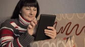 sólido : Close up of a relaxed girl using a tablet. Young woman warm striped sweater on a couch interacting with a tablet pc or e-reader. Beautiful girl using a digital laptop at home.