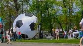 balon : People in day festival in city park. Time lapse. Crowd of tourists go for a summer day near a big soccer ball. Timelapse. Wideo