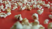 выпивка : Close up popcorn falling on red floor. Slow motion. Closeup. Fresh fluffy popcorn falling on authentic red table. Стоковые видеозаписи